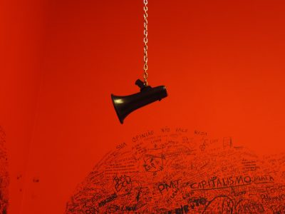 A black megaphone on a a gold chain with a red background littered with graffiti.