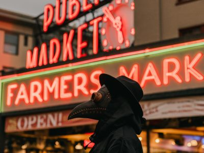 """A figure dressed as a plague doctor in front of a building with a sign saying """"Farmers Mark""""."""