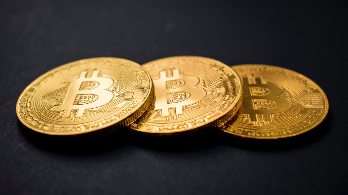 Three gold coins with the bitcoin logo on each. The coins are overlapping each other.
