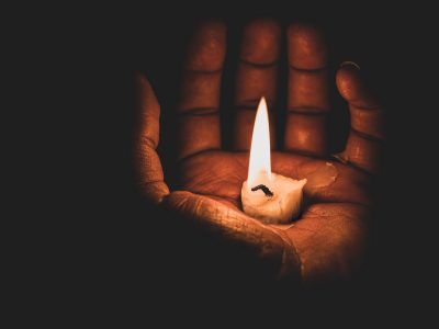 Palm of a hand in a dark room holding a lit candle stick.