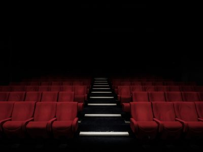 A dark theatre with rows of velvet red seats.