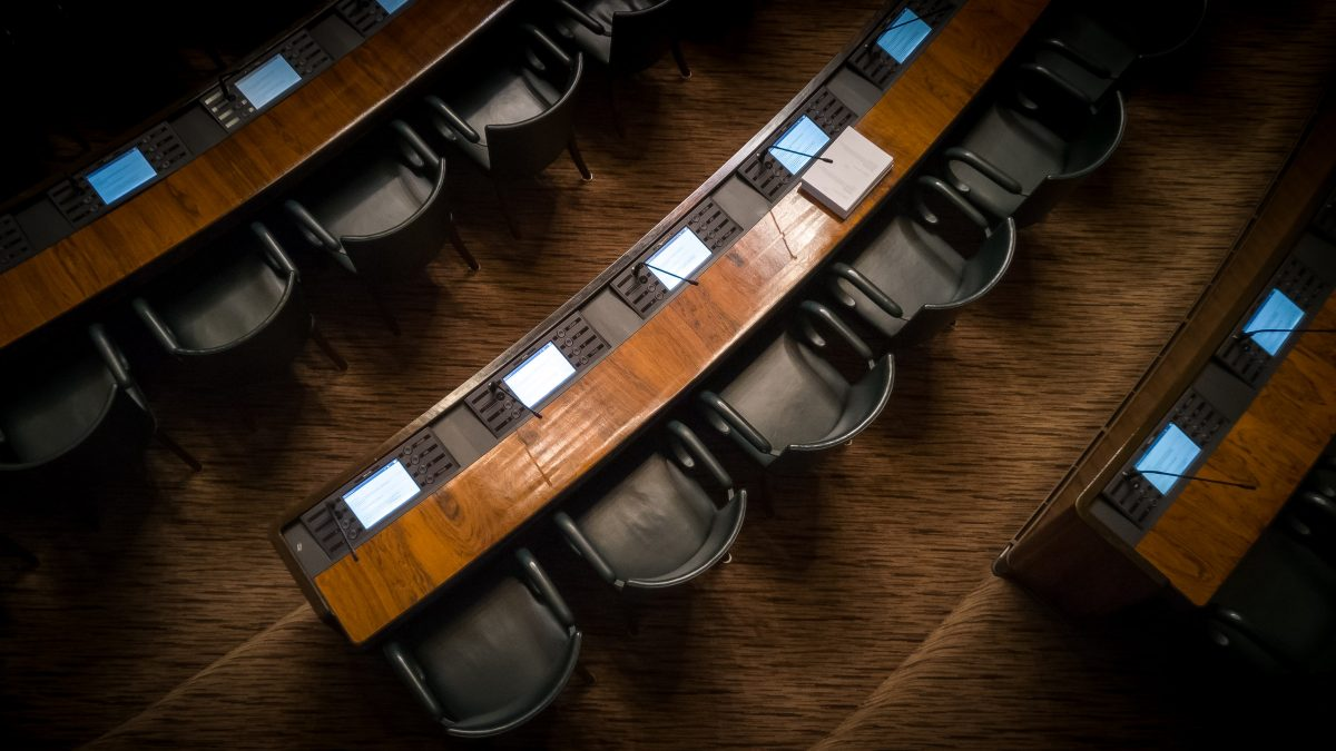 Dimly let row of chairs in a congressional setting.