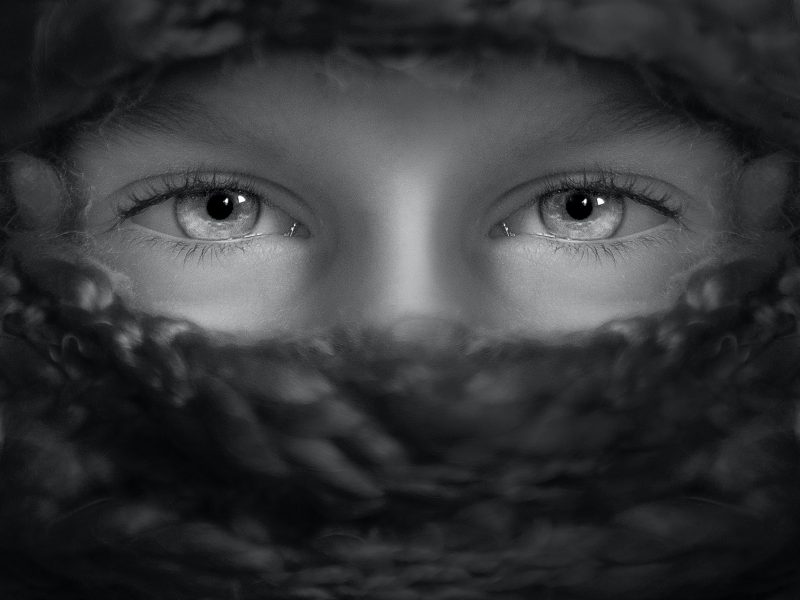 Black and white photo of a child with it's face partially covered only showing part of their nose and their full eyes.