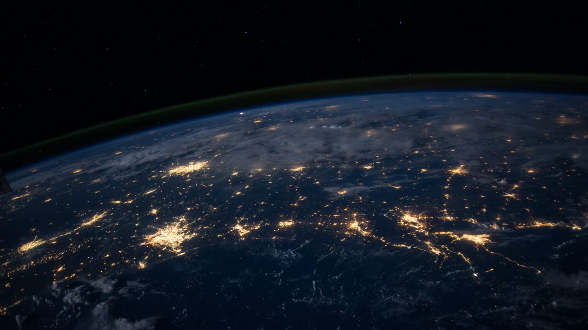 A photos from space of our planet, earth at night with different countries lit up by light.