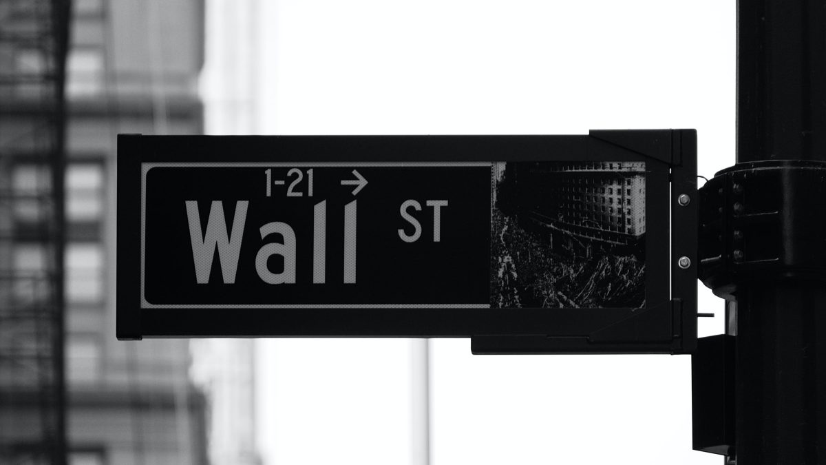 """Black and white image of a street sign showing """"1-21 Wall ST""""."""