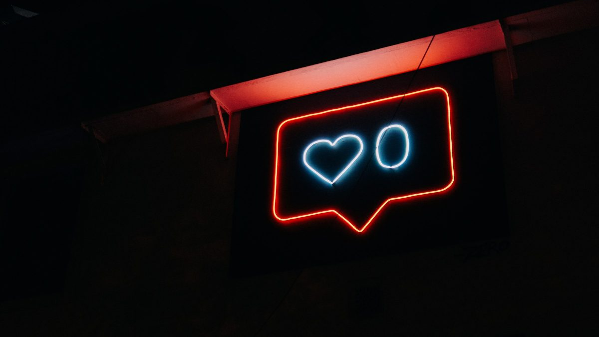 a dark image with a neon sign showing a message icon, a heart image and a zero inside the message icon.