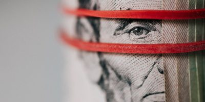 Roll of $5 bills with a red rubber band over Lincoln's face.
