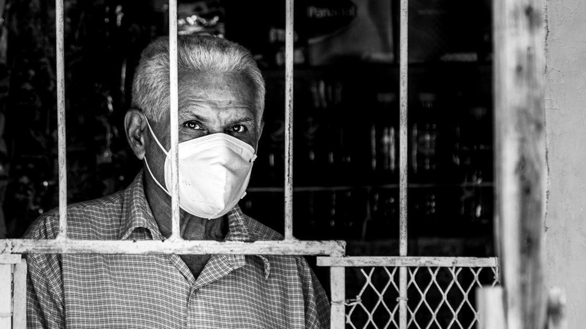old man standing behind a window while wearing a mask